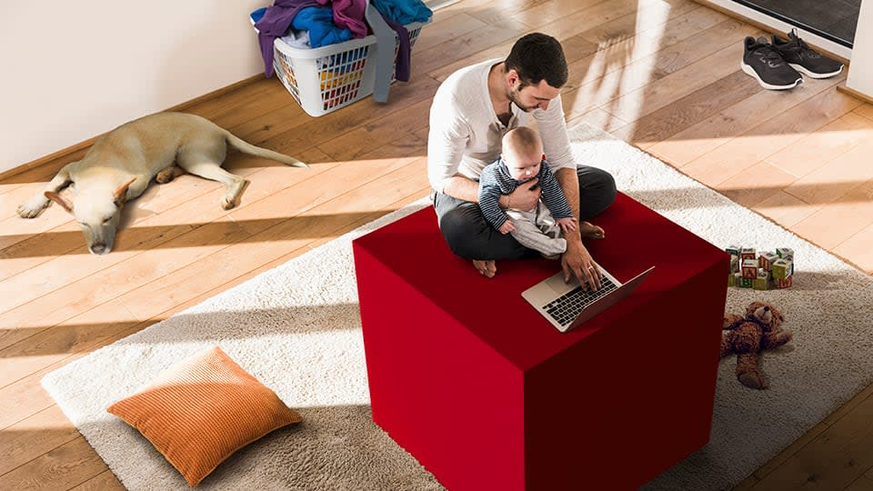 man sitting on ping box with laptop and baby