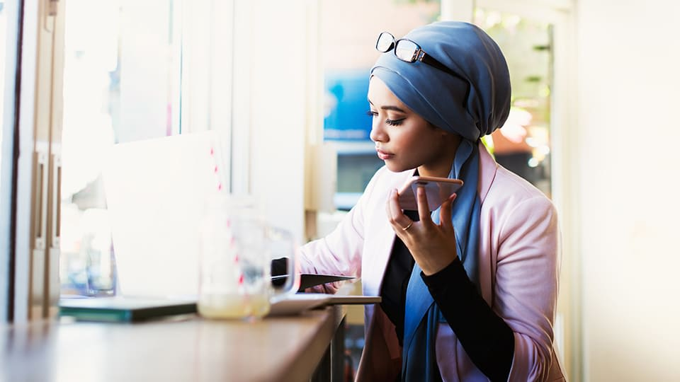 woman with headscarf using laptop and mobile phone