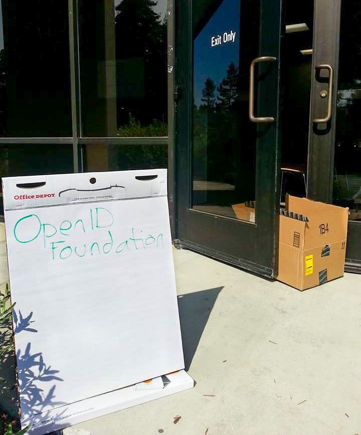 Picture of a sign reading OpenID Foundation in front of a door being propped open with a box.
