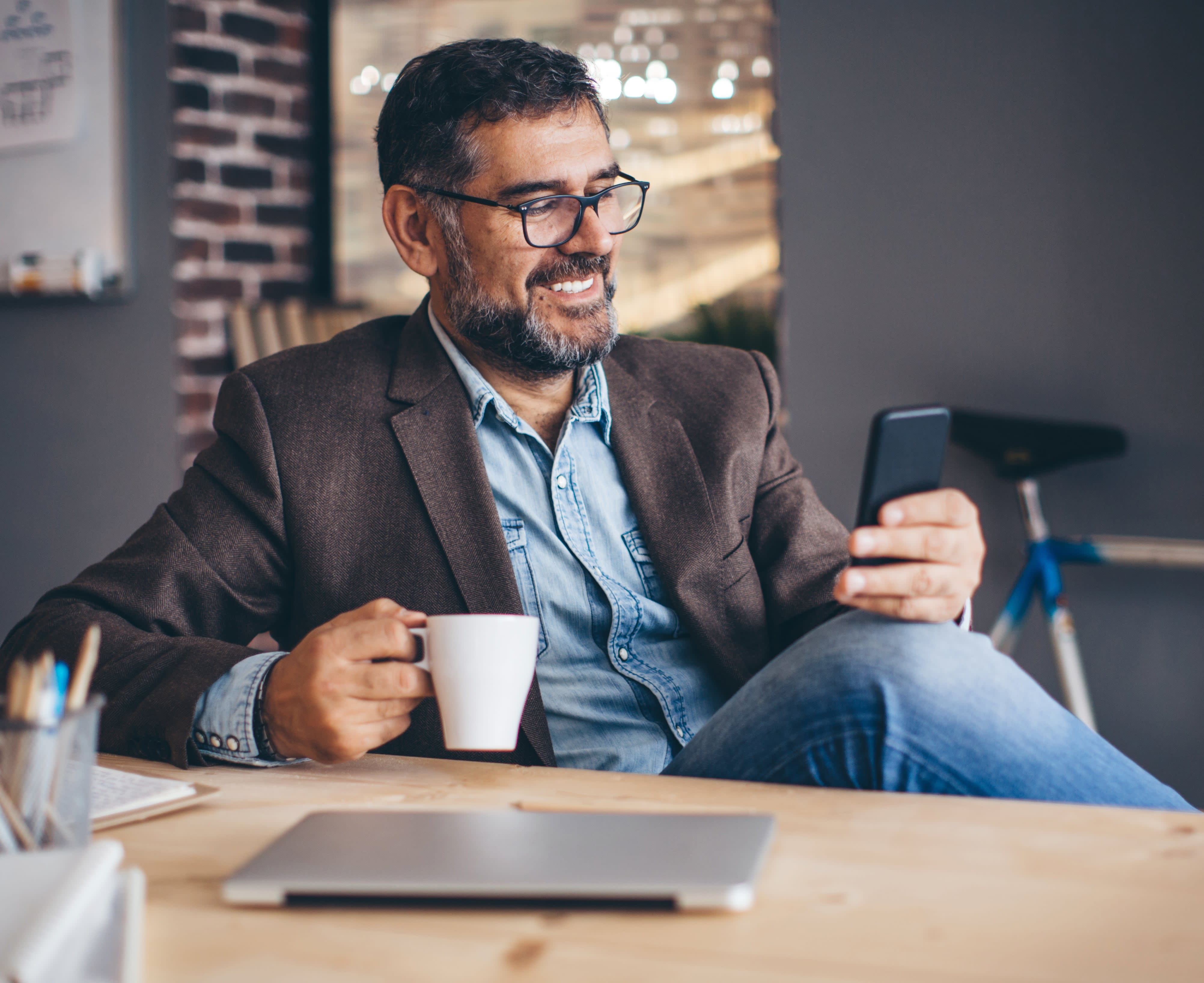 Man with cup of coffee looking at mobile phone